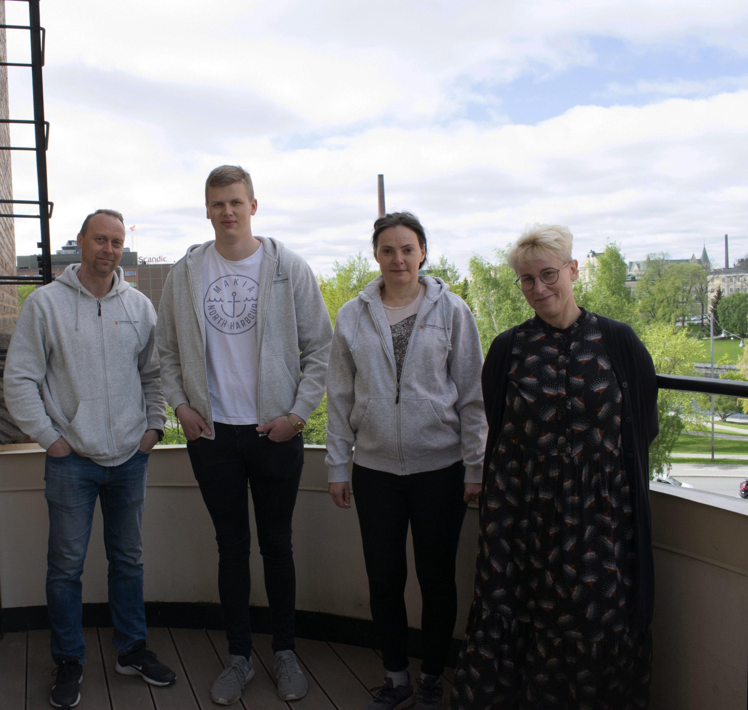 Neljä ihmistä seisoo vierekkäin parvekkeella, taustalla kaupunkimaisema.